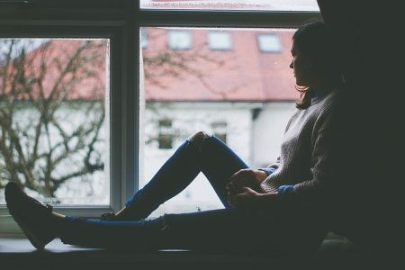 depressed woman sitting at window