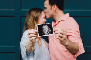 Couple holding ultrasound picture of baby